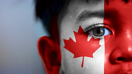 Boy's face, looking at camera, cropped view with digitally placed Canada flag on his face.